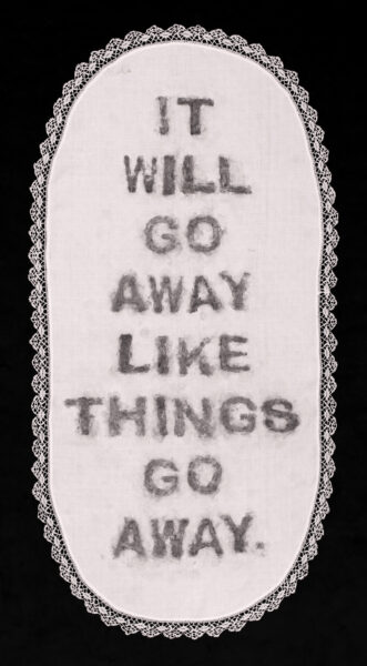 "artwork displaying the remnants of charcoal soap letters on a white vintage tablecloth with lace border on a black background. The letters read ""It will go away like things go away,"" a quote by Donald Trump."